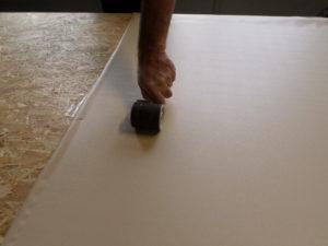 Anschließend wird die Dekorfolie mit der harten Walze so bearbeitet, daß der Kontaktkleber auch richtig packt.