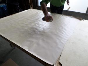 Weitere Flächen einsprühen und wieder mit der Schaumstoffrolle verteilen, bis die Rückseite komplett ist
