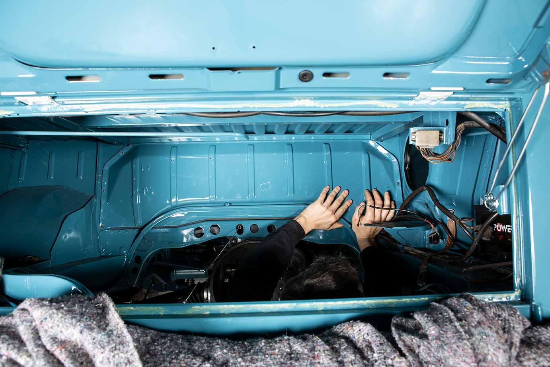 Scheinbar magische Hände im Motorraum des Bullis. Tatsächlich montiert Sebastian den Schutzschild vor dem Tank.