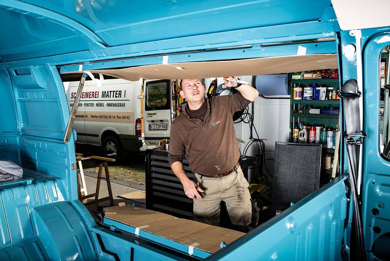 Reiner von der Schreinerei Matter in Willich prüft seine Schablonen an den Seitenklappen des Marktwagens.