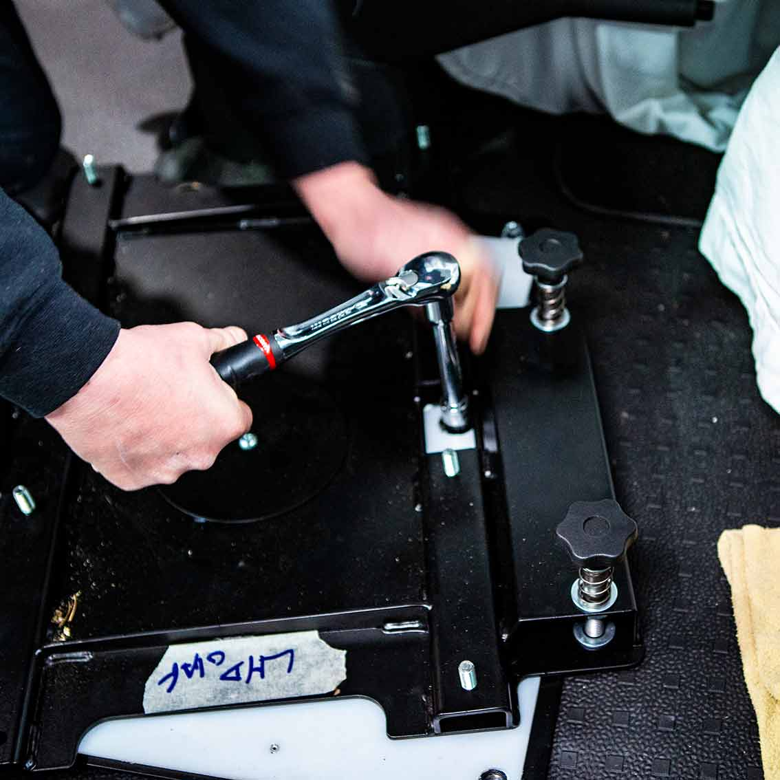 Jetzt wird die Sitzkonsole an die Schrauben aus dem Unterboden befestigt.