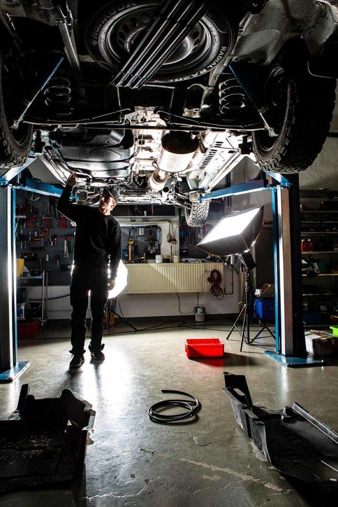 Kevin schaut unter dem VW Bus T6 nach, bevor er dort die Standheizung installiert