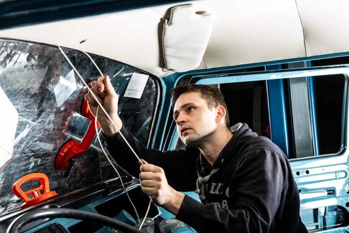 Sebastian zieht die neue Frontscheibe bei unserem VW Bus T2 Marktwagen Toni ein.
