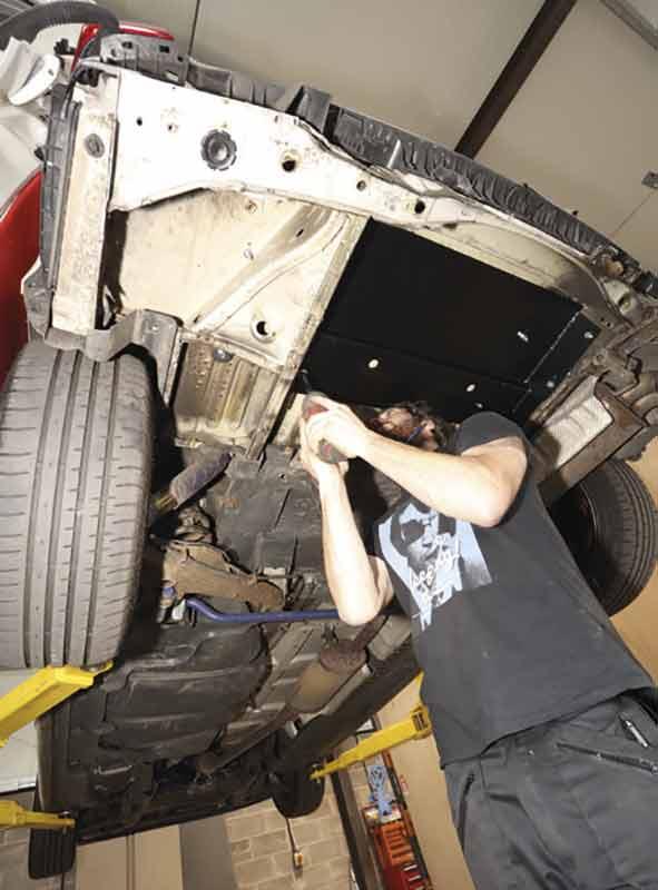 Der zweite Mann arbeitet unter dem Wagen an der Gegenplatte.
