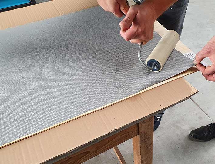 Mit hoher Kraft die Verkleidung auf die Trägerfläche andrücken.