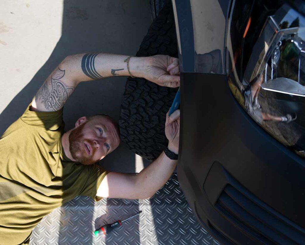 Liegende Tätigkeit: Andy von TransporterHQ löst die Befestigungen im Radkasten.