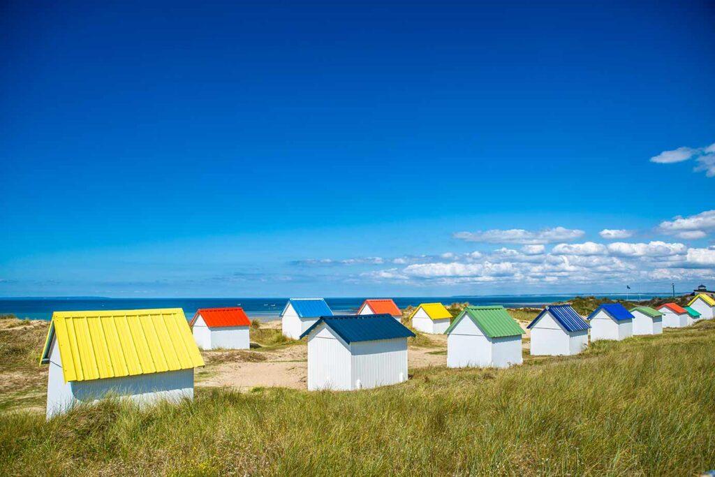 Knallbunte Dächer der Badehäuser in Gouville-sur-Mer, blaues Meer, grünes Dünengras. Mehr Strandfeeling geht kaum.