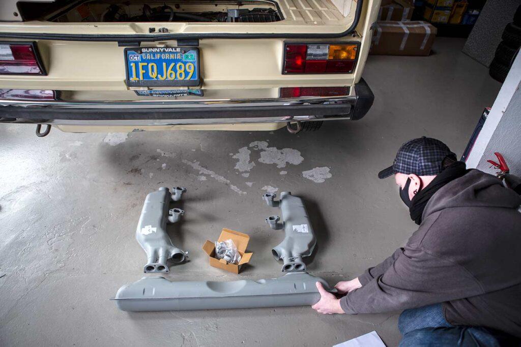Michael legt sich die Abgasanlage zurecht, die ja eigentlich nur aus dem Schalldämpfer und den Wärmetauschern besteht. Das Endrohr lassen wir hier erstmal weg.